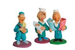 Statyetten av doktorer med tre behandla som ett barn i deras Arkivbilder