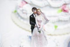 Statyetter av bruden och brudgummen på en bröllopstårta Arkivfoto