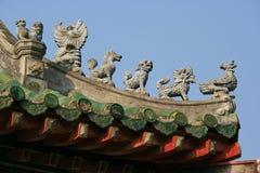 Statyetter av fantastiska djur dekorerar nocken av en tempel i Hoi An (Vietnam) Royaltyfri Foto