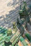 Statyetter av fantastiska djur dekorerar nocken av taket av en tempel i Peking (Kina) Arkivbilder