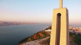StatyKristus konungen Cristo Rei Lisbon Almada på den flyg- sikten för solnedgång arkivfilmer