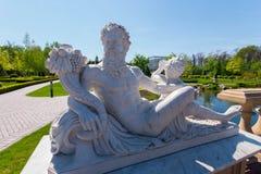 Statyn av Dionysus med en bukett av druvor på bakgrunden av en grön flotta parkerar med ett djupt rent damm Symbol av royaltyfria foton