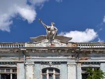 Statyn av en man med en bevingad hjälm på dess huvud och med en personal i dess hand som rider en stor fågel, smyckar taket av et arkivfoton