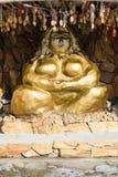 Statyn av ett guld- kvinnasammanträde i en lotusblomma poserar med etniska prydnader royaltyfri foto