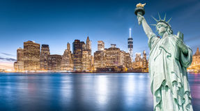 Statyn av frihet med Lower Manhattanbakgrund i aftonen Arkivfoto