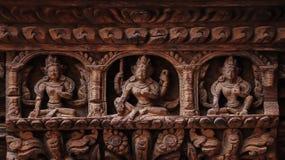 Statyn av hinduiska gudar och gudinnor sned på trädörren royaltyfria bilder