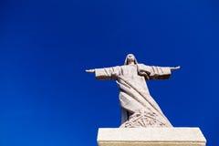 Statyn av Jesus Christ med en bakgrund för blå himmel Arkivfoton