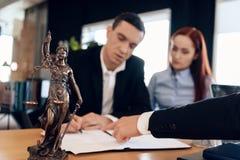 Statyn av Themis rymmer våg av rättvisa I unfocused bakgrund undertecknar den vuxna mannen dokument Royaltyfri Foto