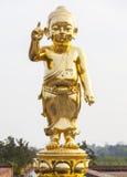 Statyn för behandla som ett barnBuddhaguld Arkivfoton