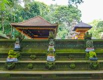 Statyn i den hinduiska templet i den Ubud apaskogen som täckas av mossa, Bali ö, Indonesien royaltyfria bilder