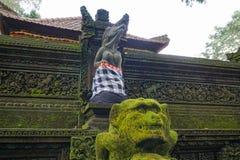 Statyn i den hinduiska templet i den Ubud apaskogen som t?ckas av mossa, Bali ?, Indonesien arkivfoto
