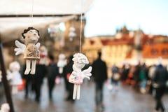 Statysouvenir i form av en ängel som hänger på bakgrunden av Prague en oskarp folkmassa av folk Royaltyfria Bilder