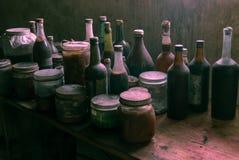 Staubige alte Glasflaschen mit sehr misstrauischem Inhalt lizenzfreies stockbild