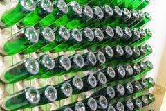 Staubige grüne Flaschen Sekt werden schräg auf Holzregalen gealtert stockbilder