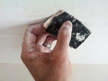 Staubige Hand, die eine weiße Oberfläche versandet Stockfotos