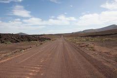 Staubige Straße durch Wüste Stockfoto