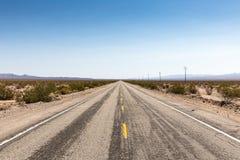Staubiger Landstraßenweg 66 führt durch die Mojavewüste, Californ stockfoto
