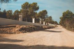 Staubiger verlassener spanischer Schotterweg zeichnete durch eine weiße Wand und grünen Bäume Stockfotografie