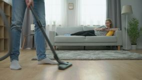 Staubsaugender Parkettboden des Mannes und seine Freundin, die Smartphone auf Couch verwendet stock footage
