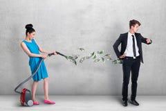 Staubsaugendes Geld der Frau aus der Tasche des Mannes heraus Lizenzfreie Stockfotos