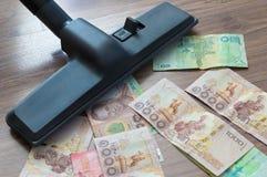 Staubsauger saugt auf Banknote stockfoto