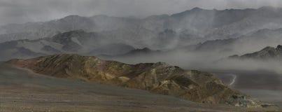 Staubsturm im Fluss Indus-Tal: Gebirgsrücken umgibt den sandigen Wind, Dunst im Tal, Steinkante im Vordergrund, Lizenzfreie Stockbilder