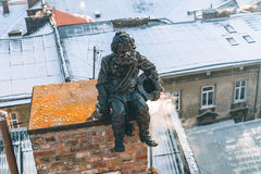Staute of chimney sweep. On the roof Royalty Free Stock Image