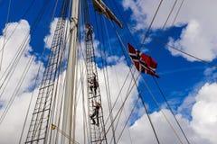STAVANGER, NOORWEGEN - CIRCA SEPTEMBER 2016: Drie bemanningsleden beklimmen op een Noorse schip` s mast stock foto's