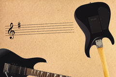 Stave and black electric rock guitar and back of guitar body on rough cardboard background. Stock Image