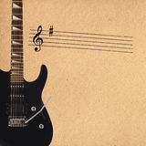Stave and black electric rock guitar on the left side of rough cardboard background. Royalty Free Stock Photography