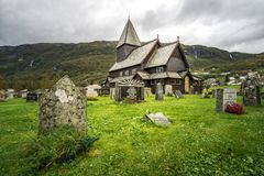 Stave church and cemetery of Roldal in dramatic light on a rainy moody day. Norway. Royalty Free Stock Images