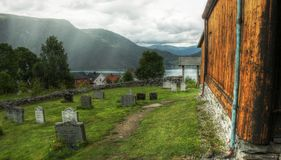 Stave Church Norway. Graveyard Fjord mountain meadow lake trees clouds Royalty Free Stock Images