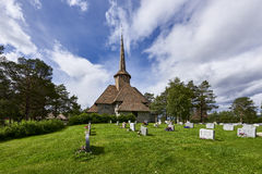 Stave church in a small town of Norway. With a green yard and a fence, as a horizontal shot Royalty Free Stock Photos