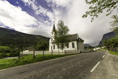 Stave Church and Street. A nice white stave church in small town of Norway, placed on a street to the mountains Royalty Free Stock Photography