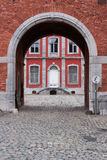 Stavelot Abbey. Cobblestone road and gate to the main building of the Stavelot Abbey seen through a archway Stock Image