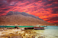 Stavros beach on Crete island, Greece. Fishing boat at sunset in Stavros bay Royalty Free Stock Photo