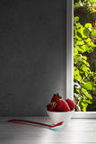 Stawberries in bowl and spoons on window sill Stock Photos