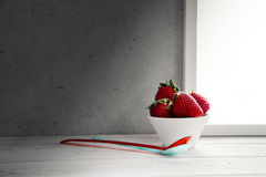 Stawberries in bowl and spoons on window sill Stock Images