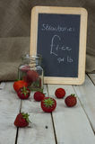 Stawberries in a jar and spilt on table Stock Image