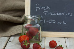 Stawberries in a jar and spilt on table Royalty Free Stock Photography