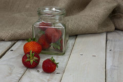 Stawberries in a jar and spilt on table Royalty Free Stock Images