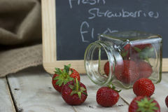Stawberries in a jar and spilt on table Stock Photo