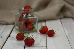 Stawberries in a jar and spilt on table Stock Images