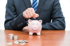 Stawiać monety w prosiątko banka pojęcie oszczędzania zdjęcie royalty free
