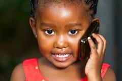 Stawia czoło strzał opowiada na telefonie komórkowym afrykańska dziewczyna. Fotografia Stock