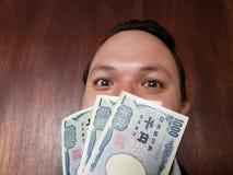 stawia czoło z emocji wyrażeniem młody człowiek i japończyków banknoty obraz royalty free