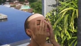 Stawia czoło zbliżenie jest ubranym purpurowych okulary przeciwsłonecznych patrzeje kamerę w nieskończoność dachu pływackim basen zbiory