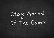 Stay ahead of the game. Text on blackboard background Stock Photography