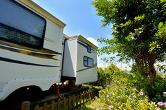 Stay in beautiful camp. Travel trailer stay in beautiful camp with tree and flower, shown as enjoy wonderful trip and holiday, or featured living environment Stock Photo