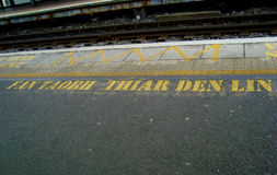 Stay behind the yellow line. Yellow text in Gaelic by the train tracks of Dublin Dart station Stock Photos